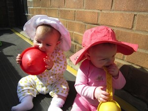 babies playing, wearing hats